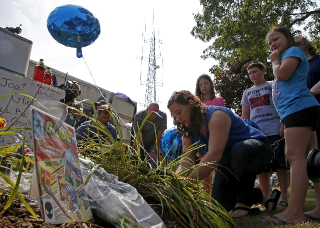 A woman ties a balloon next to a comic book at a vigil for slain Fox Lake Police Lieutenant Charles Joseph Gliniewicz in Fox Lake, Illinois, United States, September 2, 2015. Authorities in northe ...