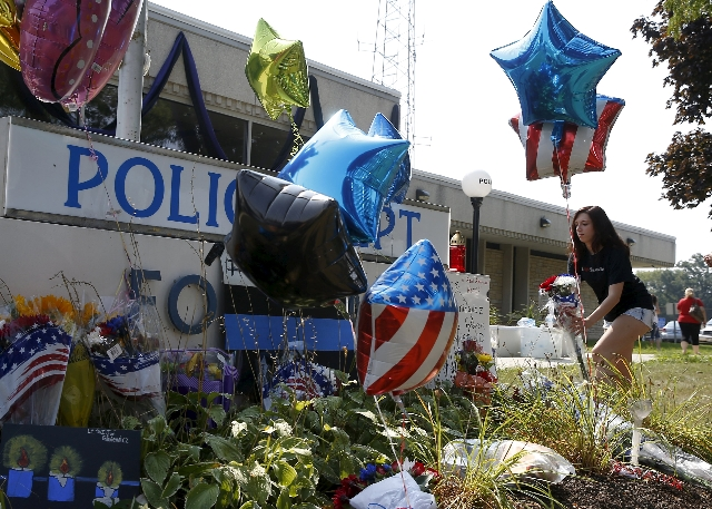 A woman lays flowers at a vigil for slain Fox Lake Police Lieutenant Charles Joseph Gliniewicz in Fox Lake, Illinois, United States, September 2, 2015. Authorities in northern Illinois expanded th ...