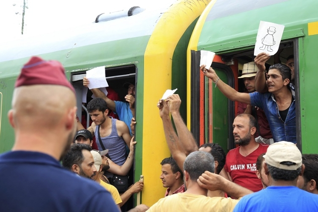 Migrants protest from inside a train at the railway station in the town of Bicske, Hungary, September 3, 2015. (Reuters/Bernadett Szabo)