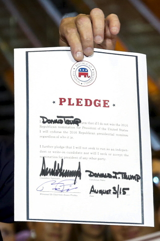U.S. presidential hopeful Donald Trump holds up a signed pledge during a press availability at Trump Tower in Manhattan, New York September 3, 2015. (Lucas Jackson/Reuters)