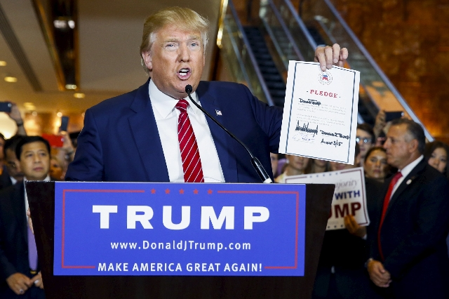U.S. presidential hopeful Donald Trump holds up a signed pledge during a press availability at Trump Tower in Manhattan, New York September 3, 2015. Trump is expected on Thursday to sign a pledge  ...