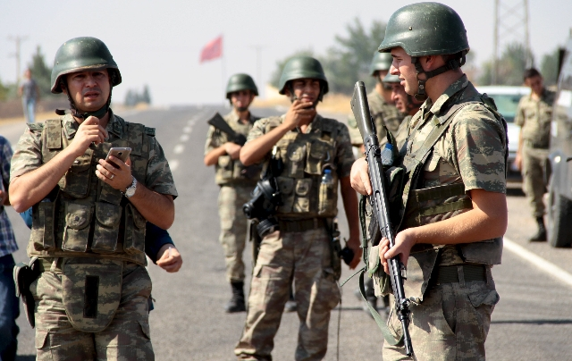 Turkish soldiers stand guard as a funeral convoy, carrying coffins of drowned Syrian migrants including the three-year old boy Aylan Kurdi, drives to the Turkish-Syrian border in Suruc, bordering  ...