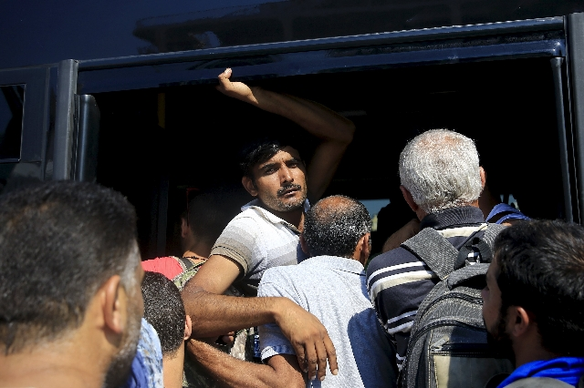 A migrant (C) is squeezed among refugees and other migrants trying to get on a bus following their arrival onboard the Eleftherios Venizelos passenger ship at the port of Piraeus near Athens, Gree ...