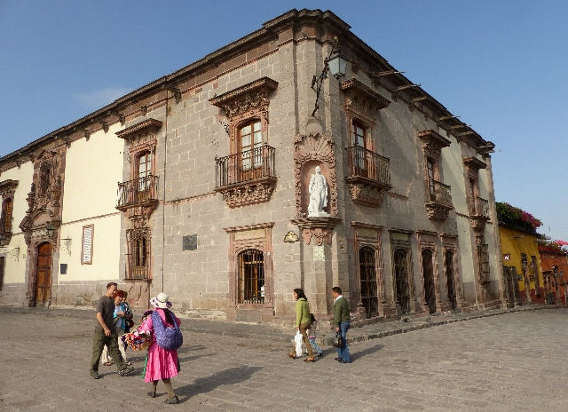 Tourists and a handicrafts seller walk past the Allende House Museum, which faces the central  square of San Miguel de Allende, Mexico, August 3, 2015. REUTERS/Walker Simon