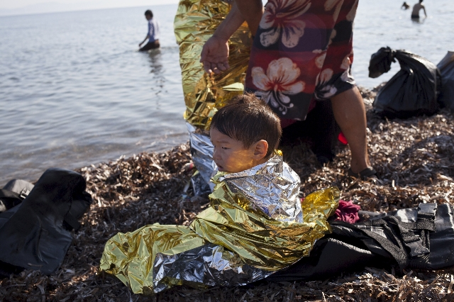 Afghan refugee child Elias, 2, from Kabul wears a thermal blanket moments after arriving on a dinghy on the Greek island of Lesbos, September 4, 2015. European Union officials are preparing to pus ...