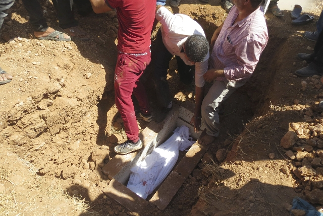 Relatives lower the body of one of two Syrian toddlers, who drowned with their mother as they were trying to reach Greece, into a grave during their funeral in the Syrian border town of Kobani Sep ...