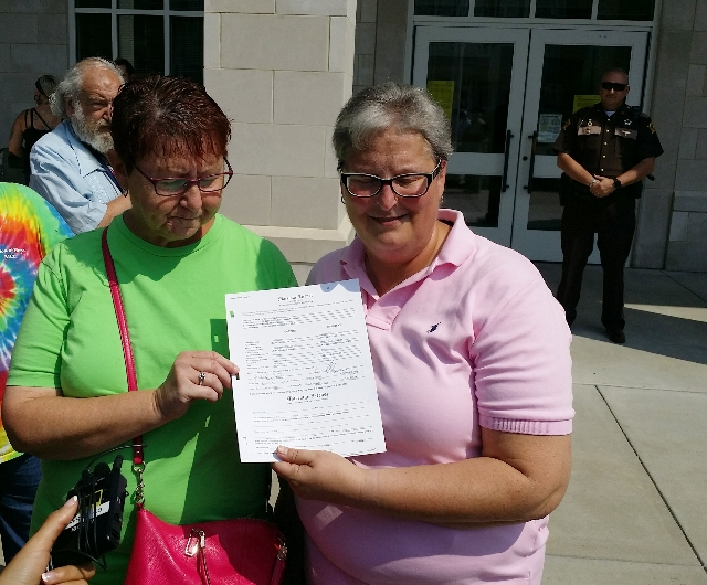 April Miller (R) and Karen Roberts speak outside the county clerk's office after obtaining a marriage license in Morehead, Kentucky, September 4, 2015. REUTERS/Steve Bittenbender
