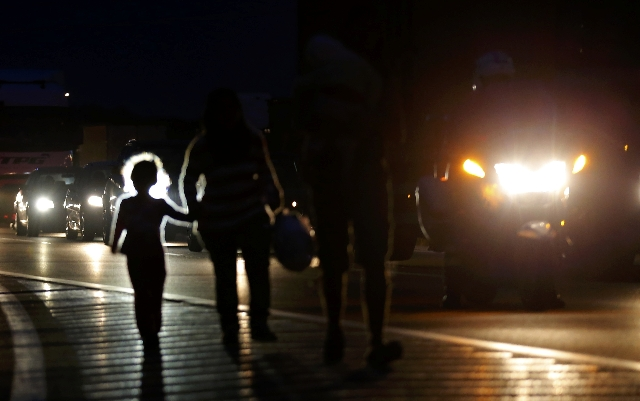 Migrants walk in the night along the highway towards the border with Austria, some 22 km of Budapest, Hungary, September 4, 2015. Migrants in Hungary, many of them Syrian refugees, broke out of a  ...