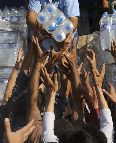 Refugees and migrants are handed out bottles of water as they wait to cross the borders of Greece with Macedonia, near the village of Idomeni September 4, 2015. European Union officials are prepar ...