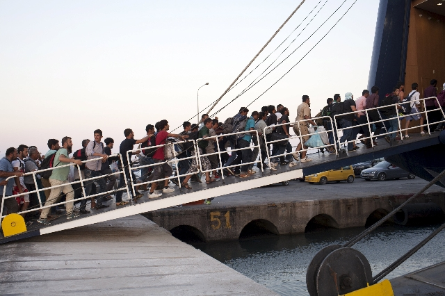 Refugees and migrants board a passenger ship heading to the port of Piraeus, at the port of Mytilene on the Greek island of Lesbos, September 4, 2015. European Union officials are preparing to pus ...