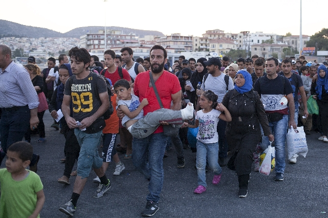 Refugees and migrants prepare to board a passenger ship heading to the port of Piraeus, at the port of Mytilene on the Greek island of Lesbos, September 4, 2015. European Union officials are prepa ...