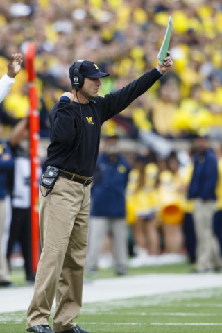 Sep 12, 2015; Ann Arbor, MI, USA; Michigan Wolverines head coach Jim Harbaugh signals in a play in the first quarter against the Oregon State Beavers at Michigan Stadium. Mandatory Credit: Rick Os ...
