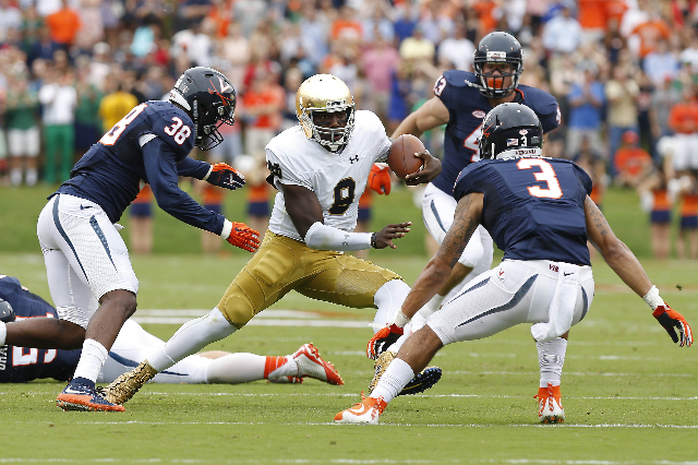 Sep 12, 2015; Charlottesville, VA, USA; Notre Dame Fighting Irish quarterback Malik Zaire (8) runs with the ball as Virginia Cavaliers safety Kelvin Rainey (38) and Cavaliers safety Quin Blanding  ...