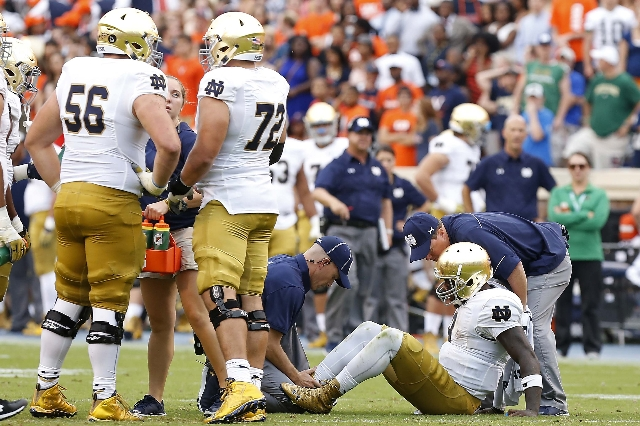 Sep 12, 2015; Charlottesville, VA, USA; Notre Dame Fighting Irish quarterback Malik Zaire (8) is examined by team trainers after injuring his right ankle against the Virginia Cavaliers in the thir ...