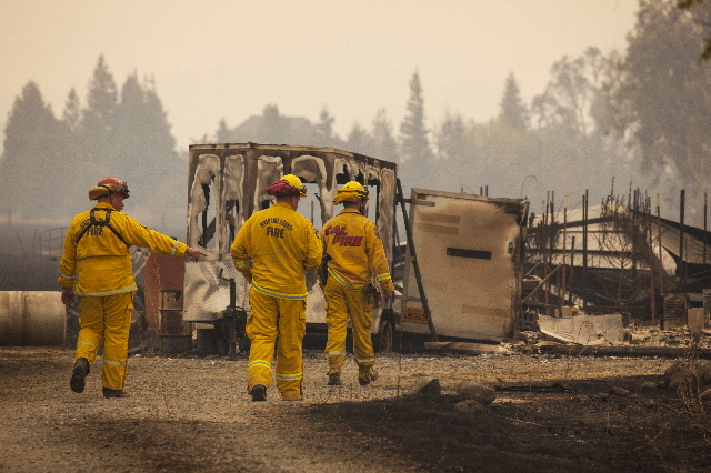 Firefighters survey a destroyed home at the so-called Valley Fire near Middleton, California September 14, 2015.  REUTERS/David Ryder