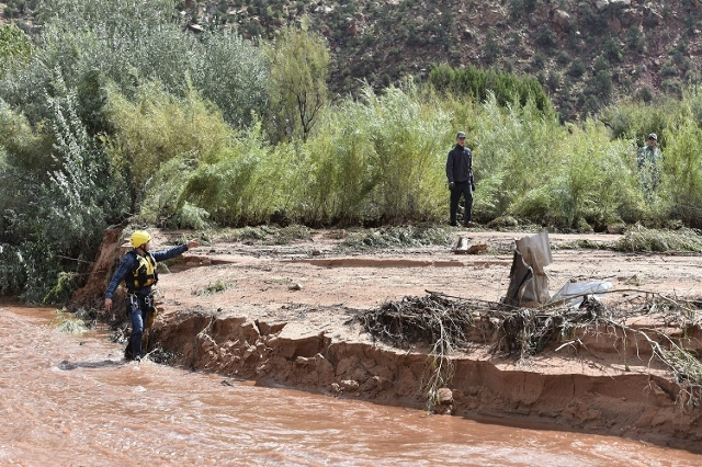 Rescuers walk along the bank of Short Creek while searching for missing residents after a flash flood in Hildale, Utah September 15, 2015. At least eight people were killed near Utah's borde ...