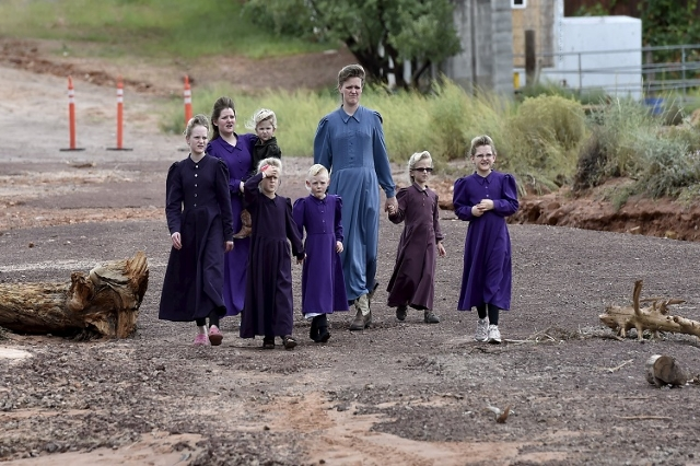 Residents walk along a street after a flash flood in Hildale, Utah September 15, 2015. At least eight people were killed near Utah's border with Arizona when flash floods triggered by heavy  ...