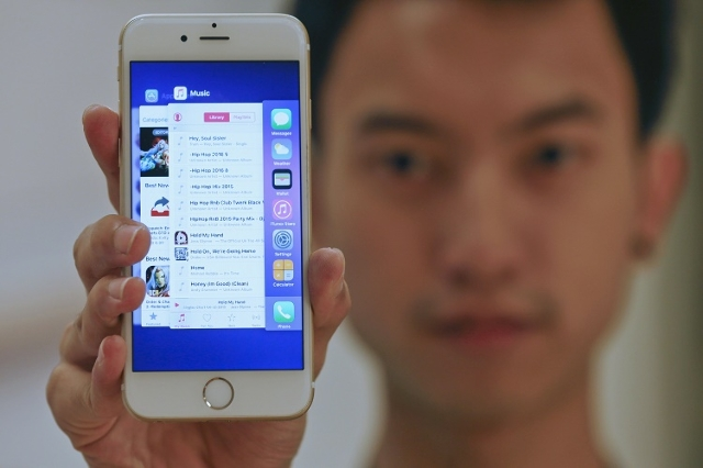 A sales assistant shows features of iOS 9 on an Apple iPhone 6 at an Apple reseller shop in Bangkok September 18, 2015. A significant number of Apple Inc customers are reporting their mobile devic ...