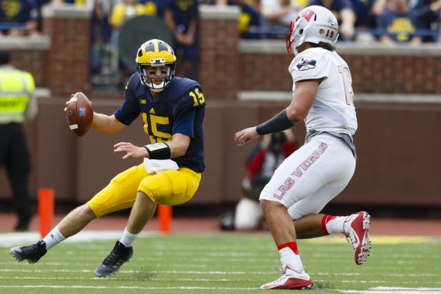 Michigan Wolverines quarterback Jake Rudock (15) scrambles from UNLV Rebels defensive lineman Mark Finau (19) in the second quarter at Michigan Stadium. (Rick Osentoski/USA TODAY Sports)