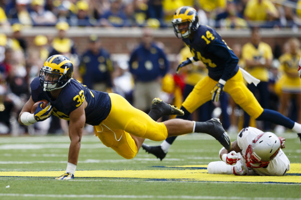 Sep 19, 2015; Ann Arbor, MI, USA; Michigan Wolverines running back Ty Isaac (32) is tripped up in the second half against the UNLV Rebels at Michigan Stadium. Michigan won 28-7. Mandatory Credit:  ...