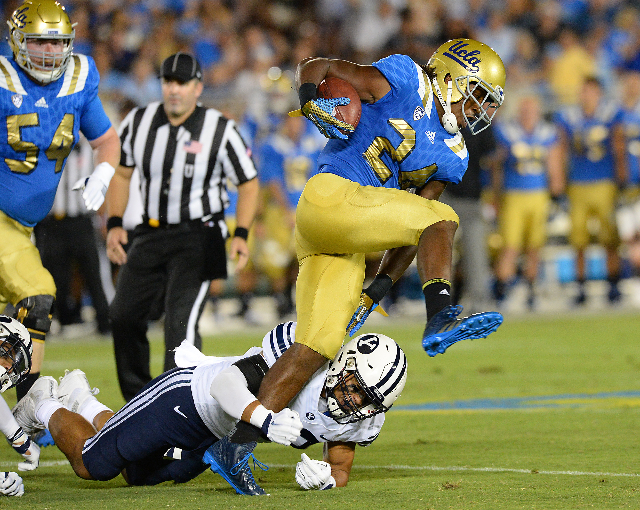 Sep 19, 2015; Pasadena, CA, USA; UCLA Bruins running back Paul Perkins (24) breaks a tackle by Brigham Young Cougars linebacker Manoa Pikula (22) for a gain in the first quarter of the game  at th ...