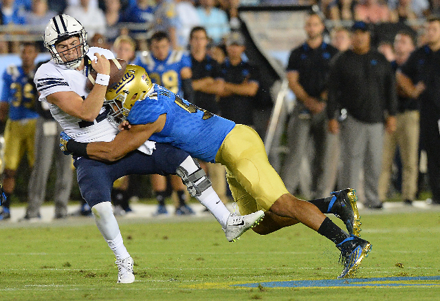Sep 19, 2015; Pasadena, CA, USA; UCLA Bruins linebacker Aaron Wallace (51) sacks Brigham Young Cougars quarterback Tanner Mangum (12) in the first quarter of the game  against the UCLA Bruins at t ...