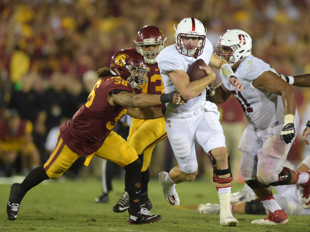 Sep 19, 2015; Los Angeles, CA, USA; Stanford Cardinal quarterback Kevin Hogan (8) is defended by Southern California Trojans linebacker Anthony Sarao (56) in the fourth quarter at Los Angeles Memo ...