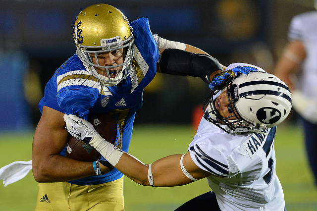 Sep 19, 2015; Pasadena, CA, USA; UCLA Bruins wide receiver Jordan Payton (9) is stopped by Brigham Young Cougars defensive back Micah Hannemann (7) after a pass play in the second quarter of the g ...