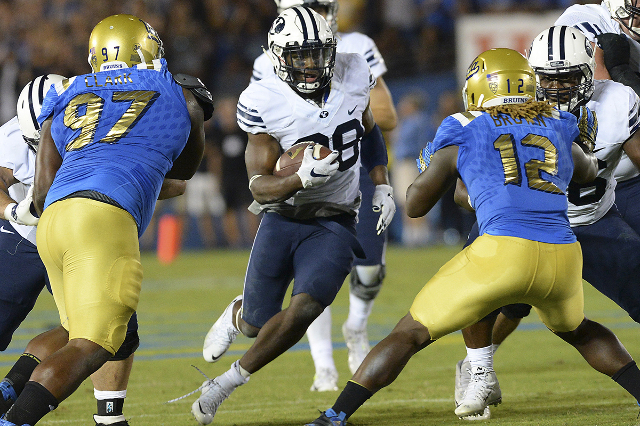 Sep 19, 2015; Pasadena, CA, USA;  Brigham Young Cougars running back Adam Hine (28) runs between UCLA Bruins defensive lineman Kenny Clark (97) and  linebacker Jayon Brown (12) for a gain in the s ...
