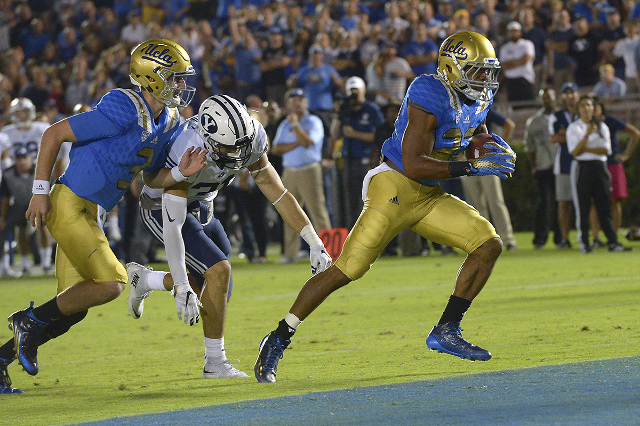 Sep 19, 2015; Pasadena, CA, USA;  UCLA Bruins quarterback Josh Rosen (3) trails the play as running back Paul Perkins (24) breaks from BYU Cougars linebacker Sae Tautu (31) to score a touchdown in ...