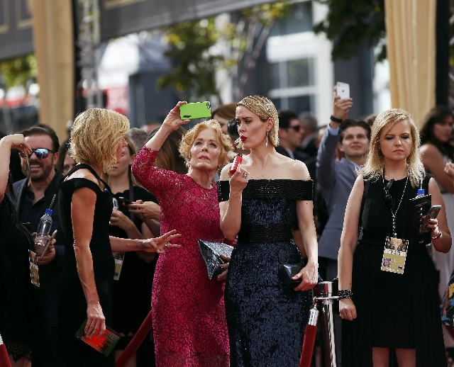 Actress Holland Taylor takes a photo as actress Sarah Paulson (2nd R)  prepares for the red carpet at the 67th Primetime Emmy Awards in Los Angeles, California September 20, 2015. (Mario Anzuoni/R ...