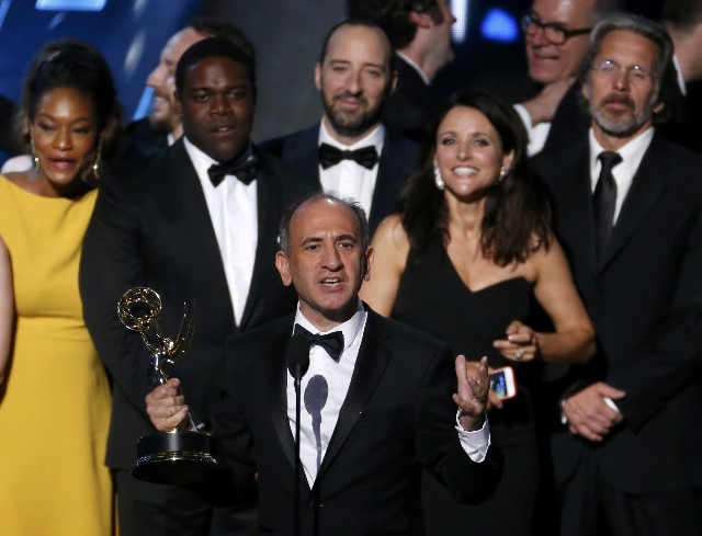 """Producer Armando Iannucci accepts the award for Outstanding Comedy Series for HBO's """"Veep"""" as show star Julia Louis-Dreyfus looks on behind him at the 67th Primetime Emmy Awards in ..."""