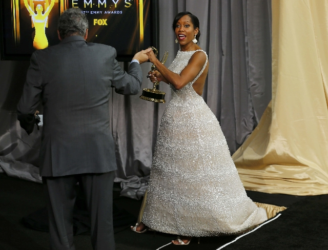 """Actress Regina King is helped offstage as she holds her award for Outstanding Supporting Actress in a Limited Series or Movie for her role on the ABC series """"American Crime"""" at the 67th  ..."""