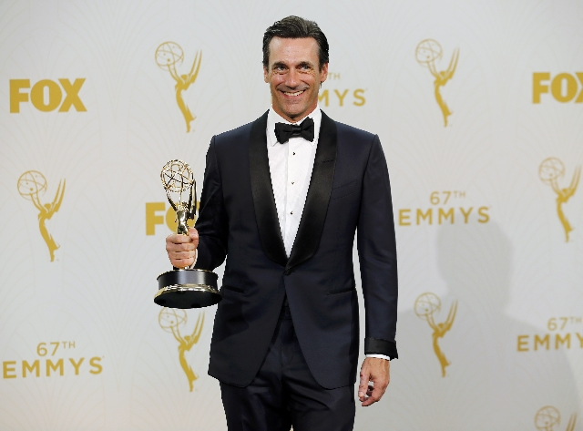 """Actor Jon Hamm holds the award for Outstanding Lead Actor In A Drama Series for AMC's """"Mad Men"""" as he walks backstage during the 67th Primetime Emmy Awards in Los Angeles, Californ ..."""