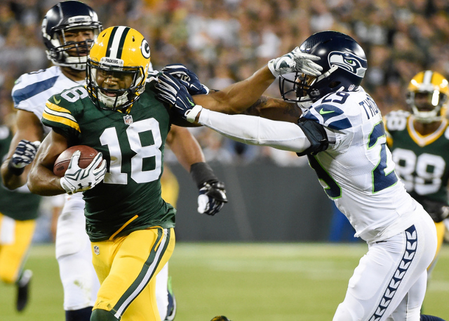 Sep 20, 2015; Green Bay, WI, USA; Green Bay Packers wide receiver Randall Cobb (18) stiff arms Seattle Seahawks safety Earl Thomas (29) after making a catch in the second quarter at Lambeau Field. ...