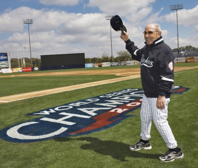 Former New York Yankees' Yogi Berra waves to the crowd before the Yankees home opener spring training baseball game against the Pittsburgh Pirates at George M. Steinbrenner Field in Tampa, F ...