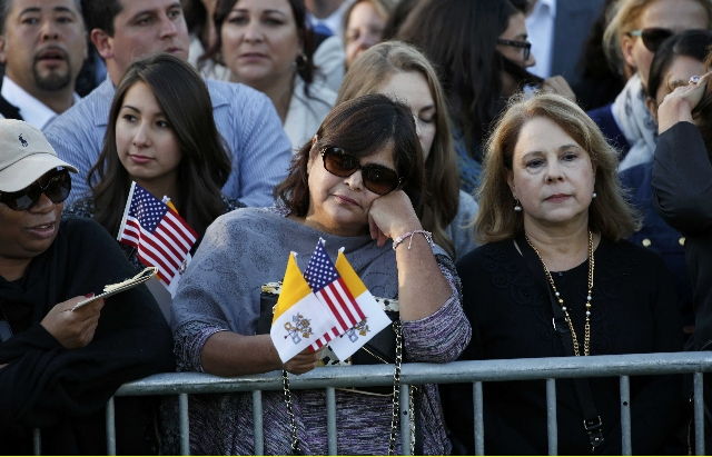 A woman holds U.S. and Vatican flags as people gather ahead of Pope Francis' meeting with U.S. President Barack Obama outside the White House in Washington September 23, 2015.  REUTERS/Kevin ...