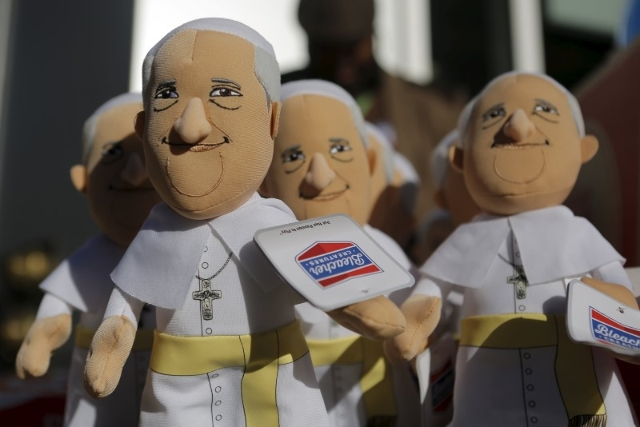 A man sells Pope Francis dolls on a street corner during the pope's visit to Washington September 23, 2015.   REUTERS/Brian Snyder
