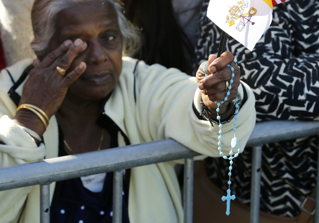 A member of the audience holds a rosary and a Vatican flag as President Barack Obama welcomes Pope Francis during a ceremony at the White House in Washington September 23, 2015. REUTERS/Jonathan Ernst