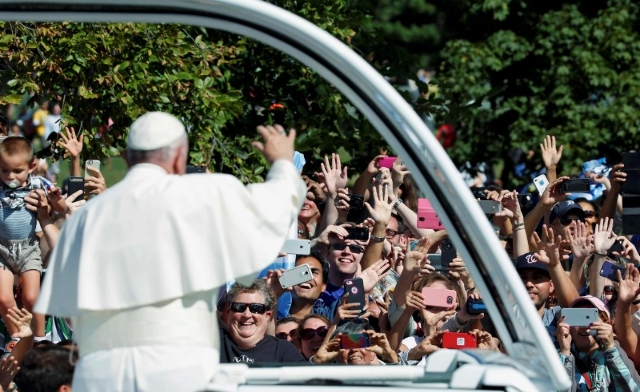 Pope Francis waves from the popemobile during a papal parade in Washington September 23, 2015.