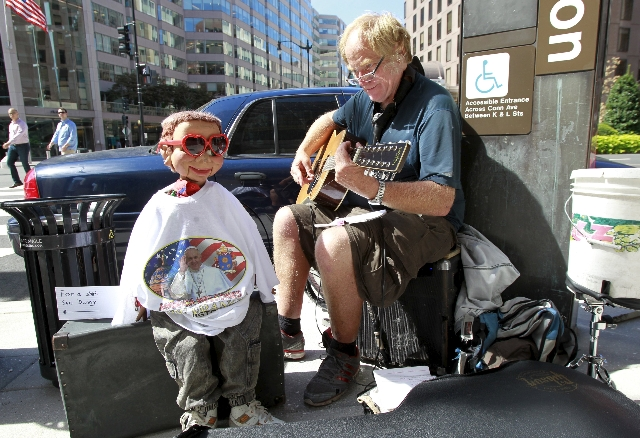 A street musician plays religious music with a doll wearing t-shirt with greetings for Pope Francis in Washington September 23, 2015. REUTERS/Yuri Gripas