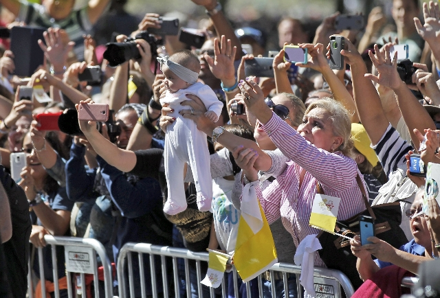 A baby is held up and as a crowd reactsduring a papal parade in Washington September 23, 2015. Pope Francis is making his first visit to the United States. REUTERS/Alex Brandon/Pool