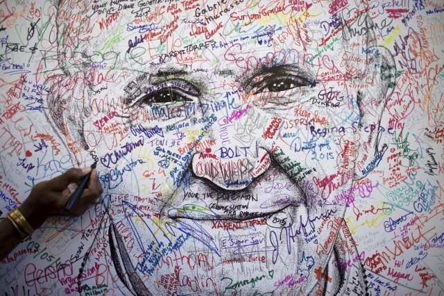 A pilgrim attending the World Meeting of Families signs a poster drawing of Pope Francis, by artist Mark Gaines, in Philadelphia, Pennsylvania, September 23, 2015.  REUTERS/Mark Makela