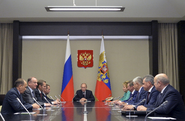 Russian President Vladimir Putin, center, chairs a meeting with members of the Security Council at the Novo-Ogaryovo state residence outside Moscow, Russia, Sept. 29, 2015. (Alexei Druzhinin/RIA N ...