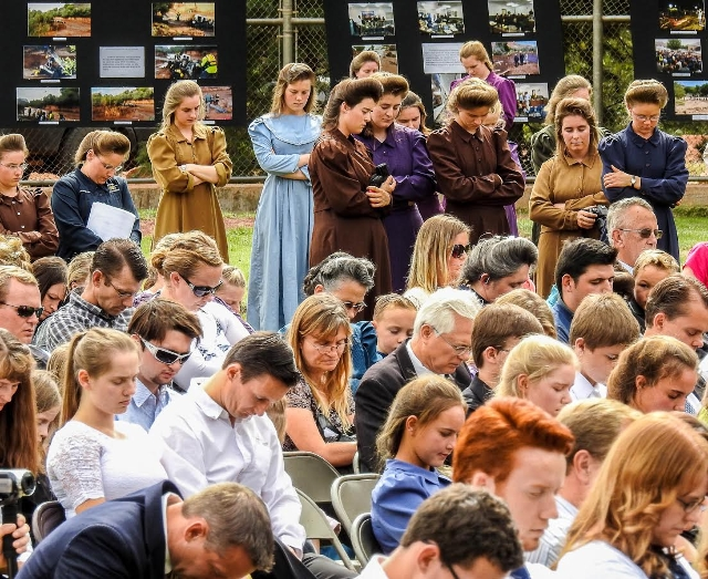 Attendees bow in prayer at a memorial for the 13 (and 1 still missing) victims of a September 14 flash flood. The memorial was held in Maxwell Park in Hildale, Utah, Saturday September 26, 2015. ( ...