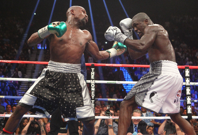 Floyd Mayweather Jr., left, and Andre Berto trade punches during their welterweight title boxing match at the MGM Grand Garden Arena in Las Vegas on Saturday, Sept. 12, 2015. Mayweather won by una ...