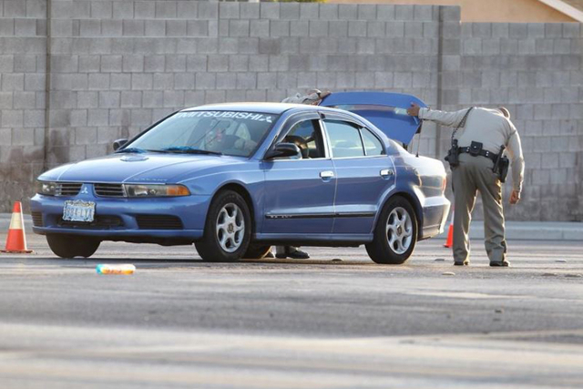 A Metro is seen checking a vehicle leaving the area Rainbow and Alta after an officer was shot early this morning. One suspect is still at large. (Kevin Cannon/Las Vegas Review-Journal)