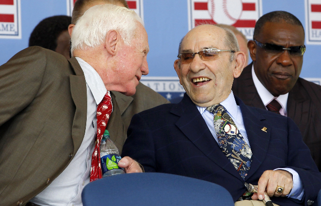 Former Major League Baseball stars for the New York Yankees and Hall of Fame members Yogi Berra (R) and Whitey Ford (L) share a laugh as they attend the National Baseball Hall of Fame induction ce ...