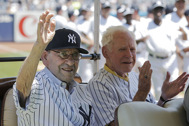 New York Yankees Hall of Famers Yogi Berra and Whitey Ford (R) reacts to fan's cheers on a golf cart during Old-Timers Day ceremonies before the Yankees played the Tampa Bay Rays in their ML ...