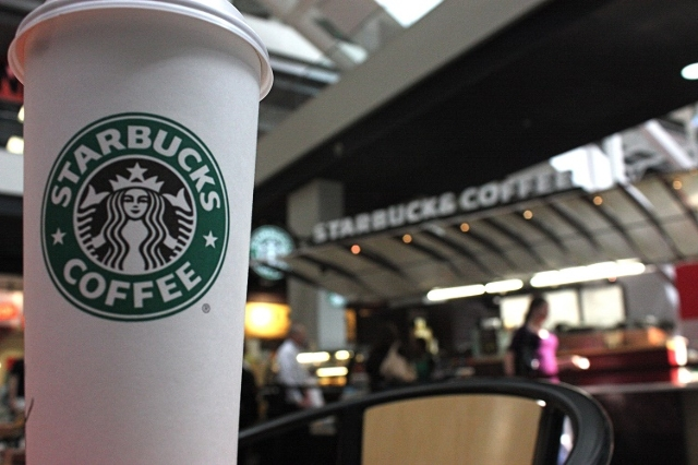 A close-up photograph showing a Starbucks cup with a kiosk in the background. (Ferre' Dollar/CNN)